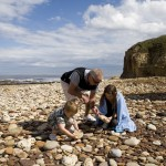 Family collecting pebbles on the beach at Blackhall