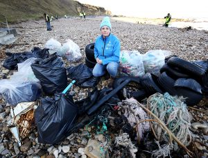 Litter picker on the beach with lots of bin bags full of rubbish